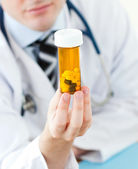 Young doctor holding pills — Stock Photo