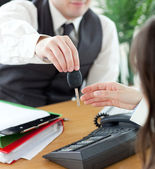 Young salesman giving car's key to his customer — Stock Photo