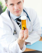 Doctor holding pills — Stock Photo
