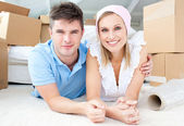 Jolly couple lying between boxes — Stock Photo