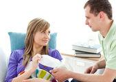Troskliwy człowiek daje jego dziewczyna źle tkanki leżące na kanapie — Zdjęcie stockowe