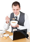 Happy businessman eating cereals looking at his laptop — Stock Photo