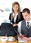 Businesswoman packing her bag businessman using laptop — Stock Photo