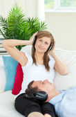 Cheerful woman listening to music with her boyfriend — Stock Photo