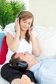 Donna carina ascoltando musica con il suo ragazzo sdraiata su un divano — Foto Stock