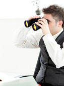 Close-up of a young businessman looking through binoculars isola — Stock Photo