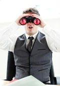 Impressed businessman looking through binoculars sitting in his — Stock Photo