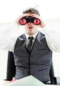 Impressed businessman looking through binoculars sitting in his — Stock Photo