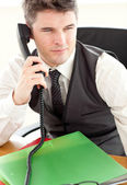 Self-assured businessman talking on phone at office — Stock Photo