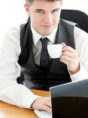 Jolly young businessman looking at the camera holding a coffee — Stock Photo