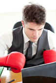 Ambitious businessman wearing boxing gloves in the office — Stock Photo