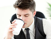 Young businessman drinking coffee in the office — Stock Photo