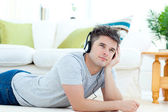 Young man with headphones lying on the floor in the living room — Stock Photo