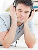 Pozitivní mladý muž poslouchat hudbu se zavřenýma očima — Stock fotografie