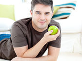Positive man holding a green apple lying on the floor — Stock Photo