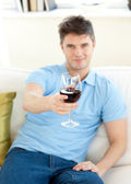 Charming young man sitting on a sofa holding wineglass — Stock Photo