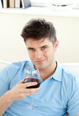 Handsome young man sitting on a sofa holding wineglass — Stock Photo