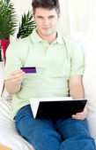 Charismatic young man with card and laptop on a sofa — Foto Stock