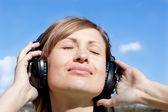 Beautiful woman listenng music outdoors — Stock Photo