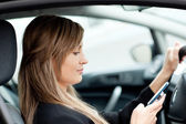 Beautiful businesswoman sending a text while driving — 图库照片