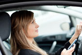 Attractive businesswoman sending a text while driving to work — Stockfoto
