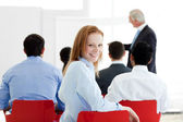 Smiling caucasian businesswoman at a conference — Stock Photo