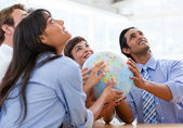 International business team holding a terrestrial globe — ストック写真