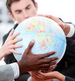 Gros plan d'une équipe de commerciaux, tenant un globe terrestre — Photo
