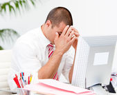Frustrated businessman working at a computer — Stock Photo