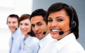 Ethnic businesswoman with headset on smiling at the camera — Stock Photo