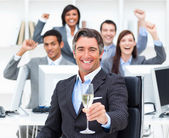 Triumphant manager and his team drinking champagne — Stock Photo