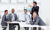 Smiling manager holding a globe with his team working at compute — Stockfoto