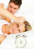Man and angry woman in bed looking at the alarm clock going off — Stock Photo