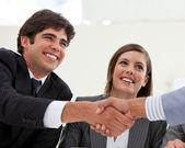 Sonriente hombre de negocios y su colega cerrando un trato con una parte — Foto de Stock