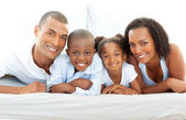 Happy family having fun lying down on bed — Stock Photo