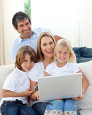 Cute children with their parents using a laptop — Stock Photo