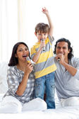 Animated family singing with microphones — Stock Photo