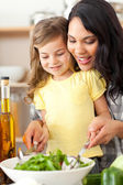 Brunette mother helping her daughter prepare salad — Stockfoto