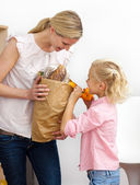 Little girl unpacking grocery bag with her mother — Stock Photo
