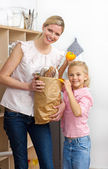 Happy mother and her Little girl unpacking grocery bag — Stock Photo