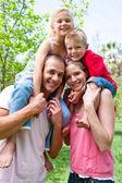 幸福的父母们给他们的孩子背驮骑 — 图库照片