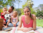 Smiling woman reading at a picnic with her family — Stock Photo