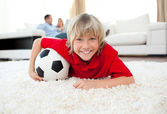 Smiling boy watching football match lying on the floor — Stock Photo
