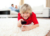 Happy boy holding a remote lying on the floor — Stock Photo