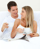 Enamored couple drinking a cup of tea lying on their bed — Stock Photo