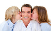 Cute siblings kissing their father — Stock Photo