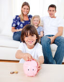 Cheerful little boy inserting coin in a piggybank — Stock Photo