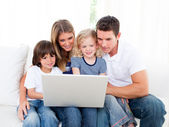 Portrait of a jolly family using a laptop sitting on sofa — Stock Photo