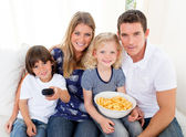 Loving family watching television sitting on sofa — Stock Photo
