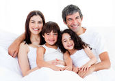 Portrait of a happy family sitting on a bed — Stock Photo